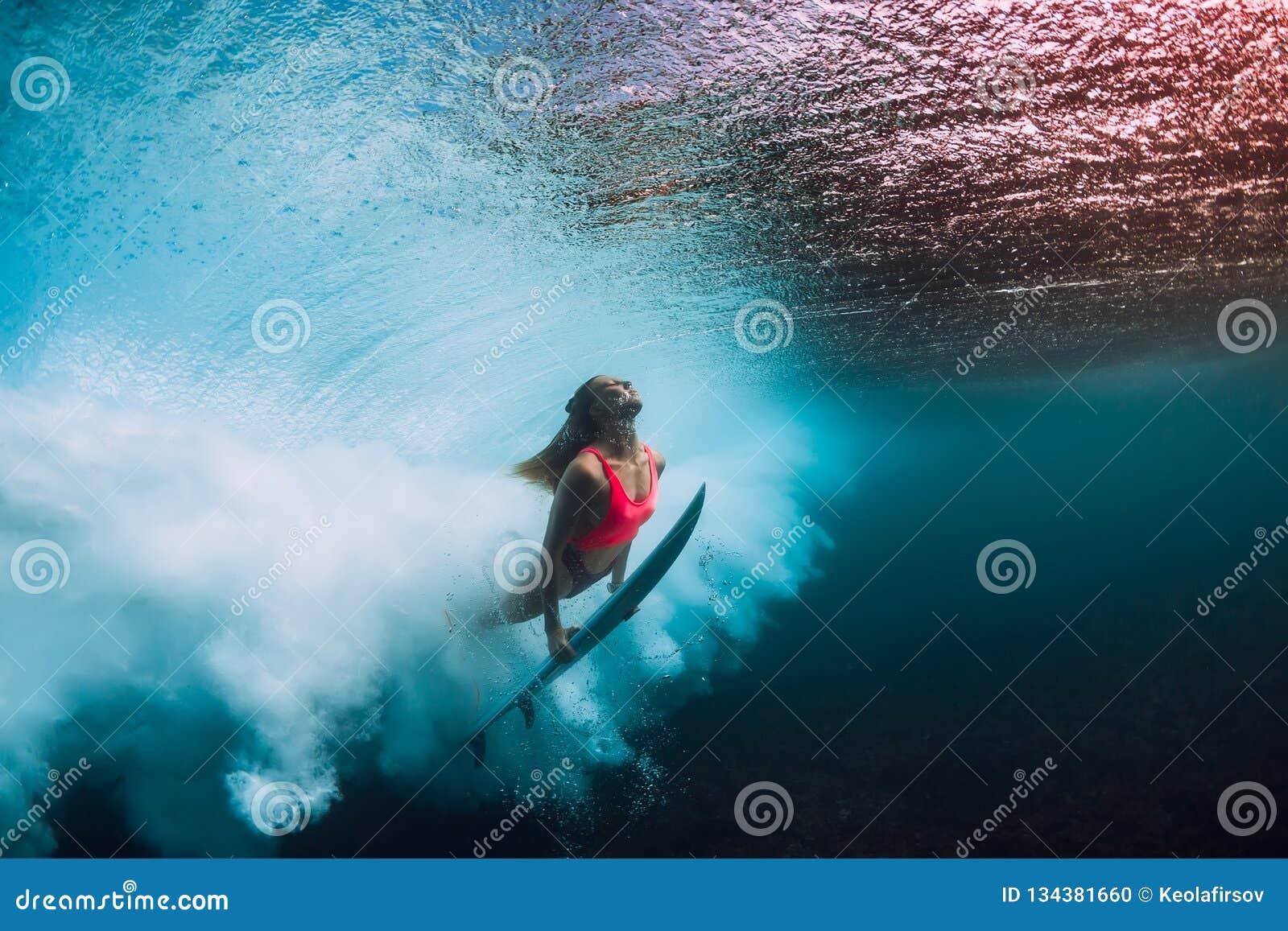 Mergulho desportivo da mulher do surfista subaquático com a onda inferior do tambor