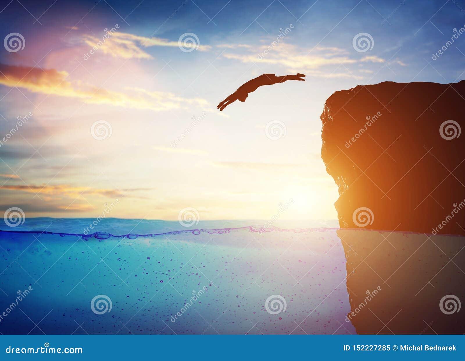 Mergulho do homem na água do penhasco alto ao desconhecido