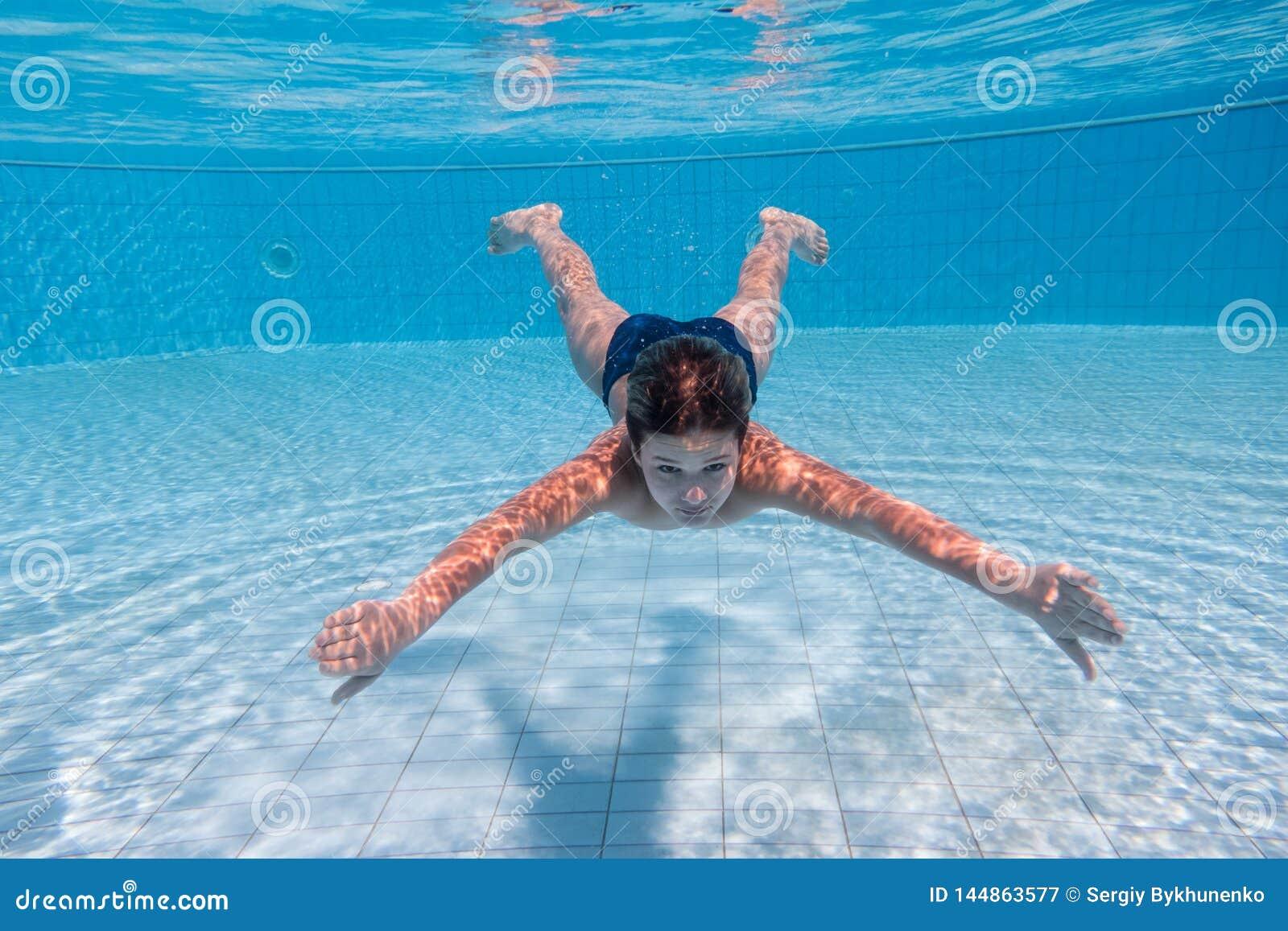 Mergulho do menino na piscina
