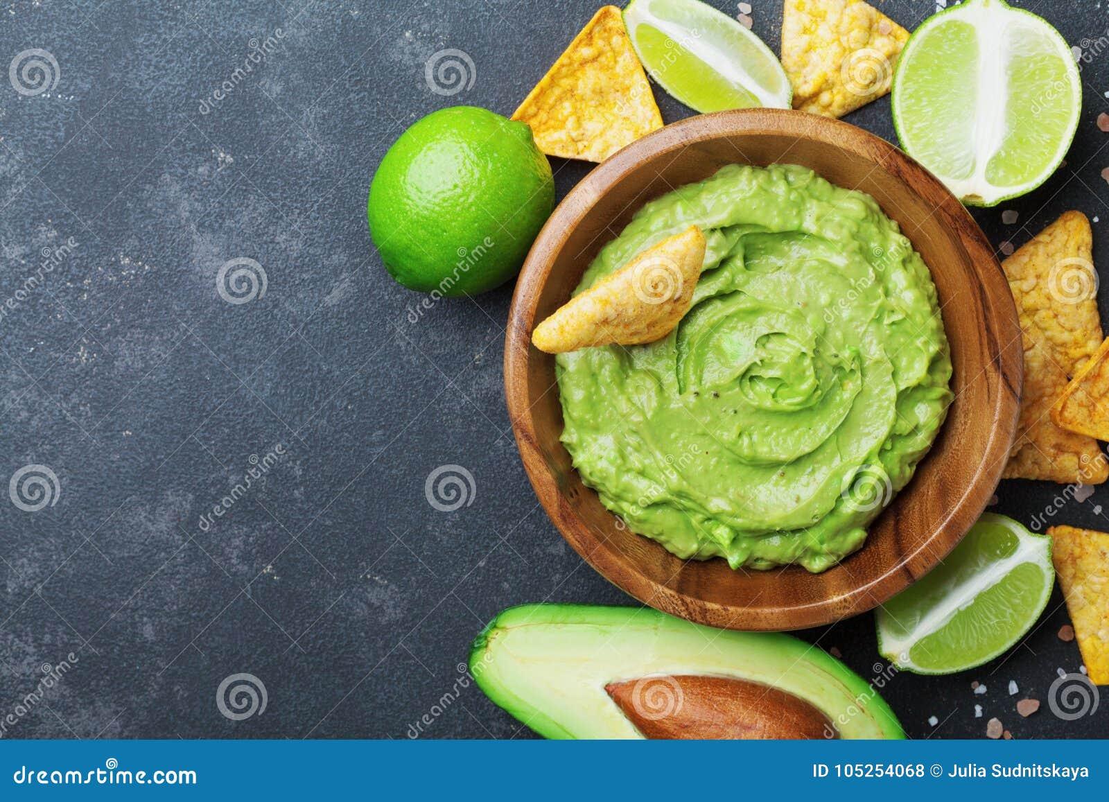Mergulho fresco do guacamole com abacate, cal e nachos na opinião de tampo da mesa preta Copie o espaço Alimento mexicano tradici