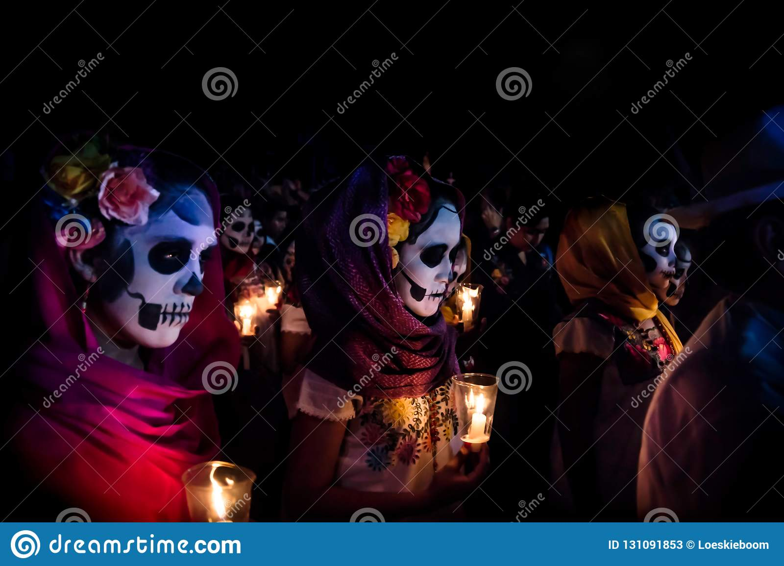 Three women with Catrina customes, scarves on their head and flowers in the hair with skull make-up holding candels surrounded by