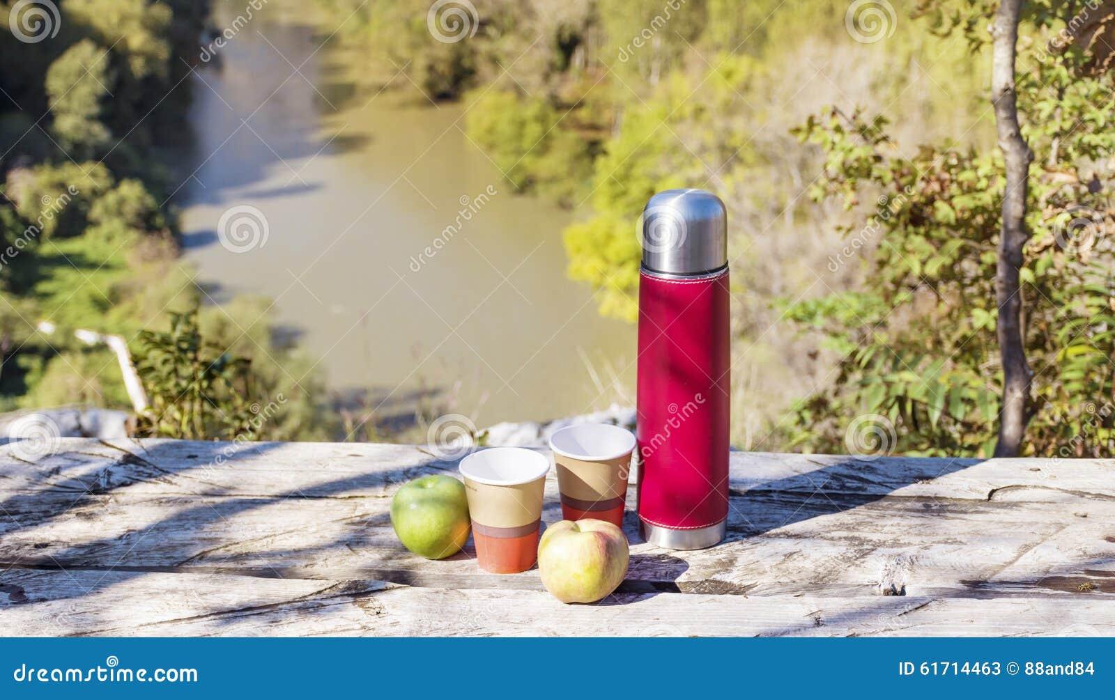 Meriende en el campo en la alta montaña con el termo, el café y manzanas rojos