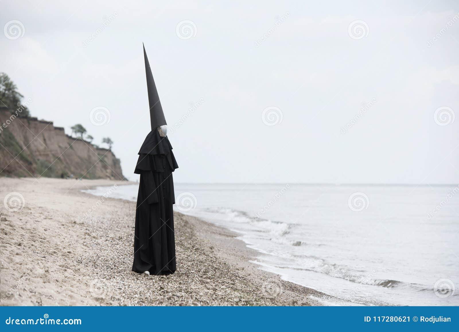 Merkwürdige Zahl im schwarzen Mantel mit der Spiegelfläche in der Küste