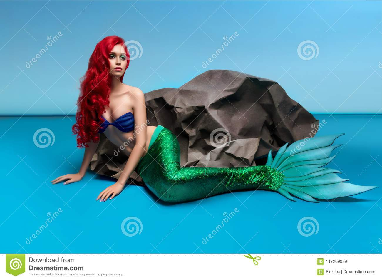Mermaid with red hair resting near stone