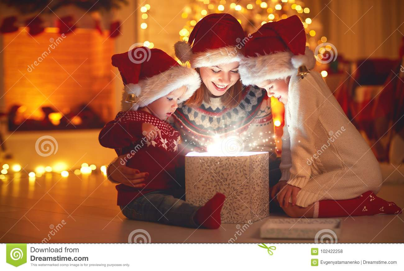 Merry Christmas! family mother and children with magic gift at