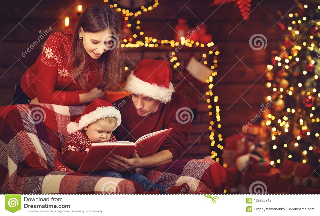 Merry Christmas! family mother father and baby read book near tr