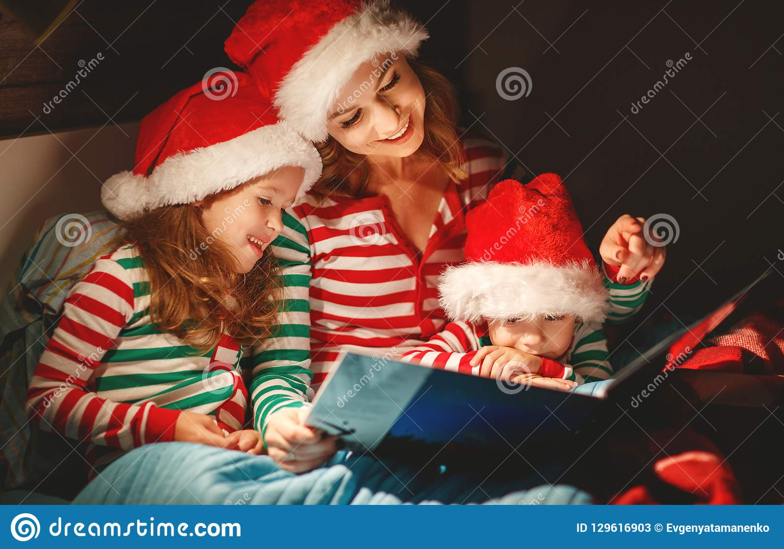 Merry Christmas! family mother reads to children book before bed