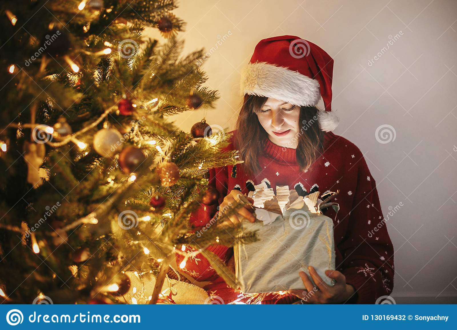 f1f7633fd4f73 Merry Christmas. Happy Girl In Santa Hat Opening Magic Christmas ...