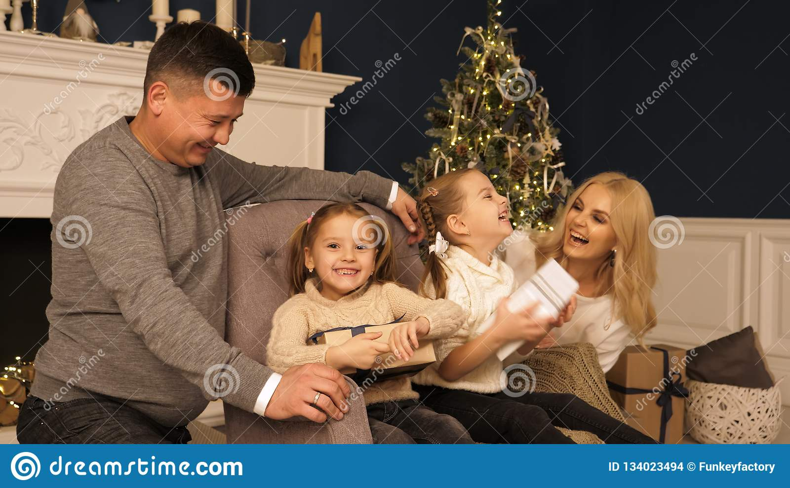 Merry Christmas and Happy Holidays! Cheerful mom and dad and cute daughters girls exchanging gifts. Parent and two