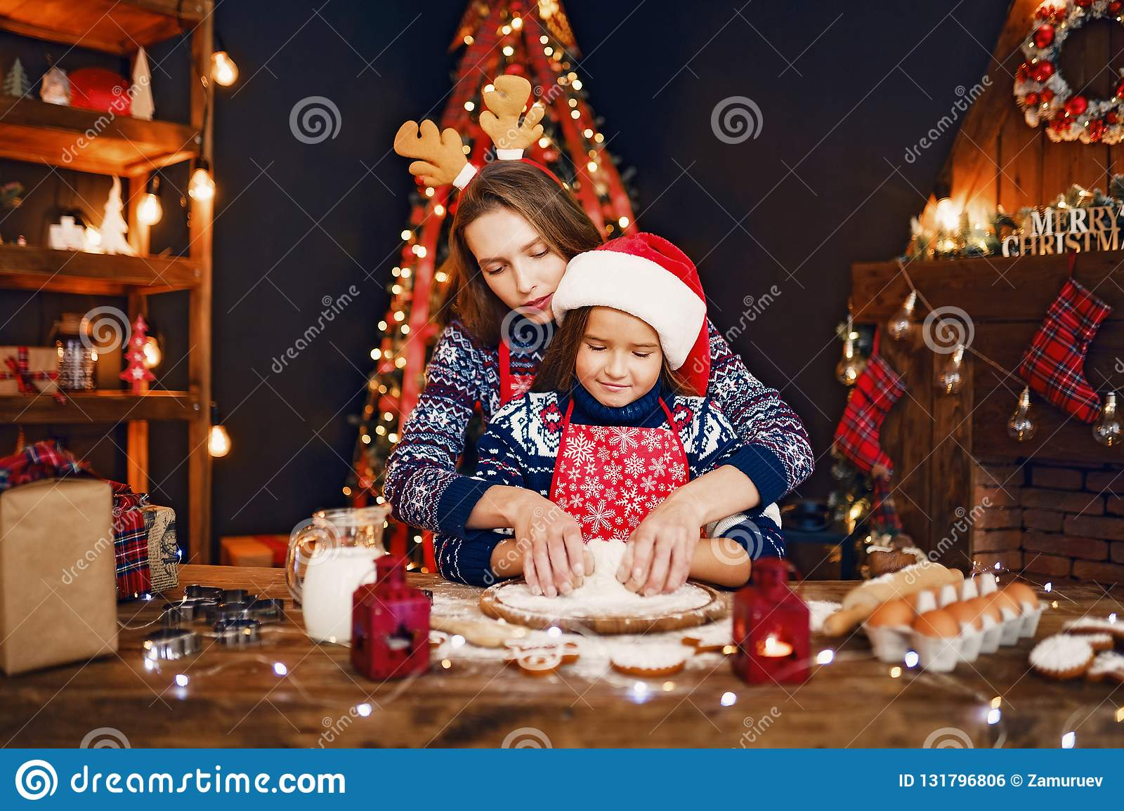 Merry Christmas and Happy Holidays. Mother and daughter cooking Christmas cookies.