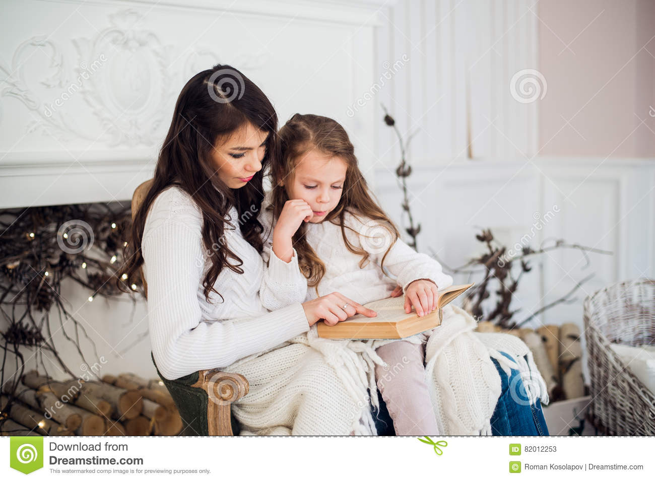Merry Christmas and Happy Holidays, Pretty young mom reading a book to her cute daughter near tree indoors.