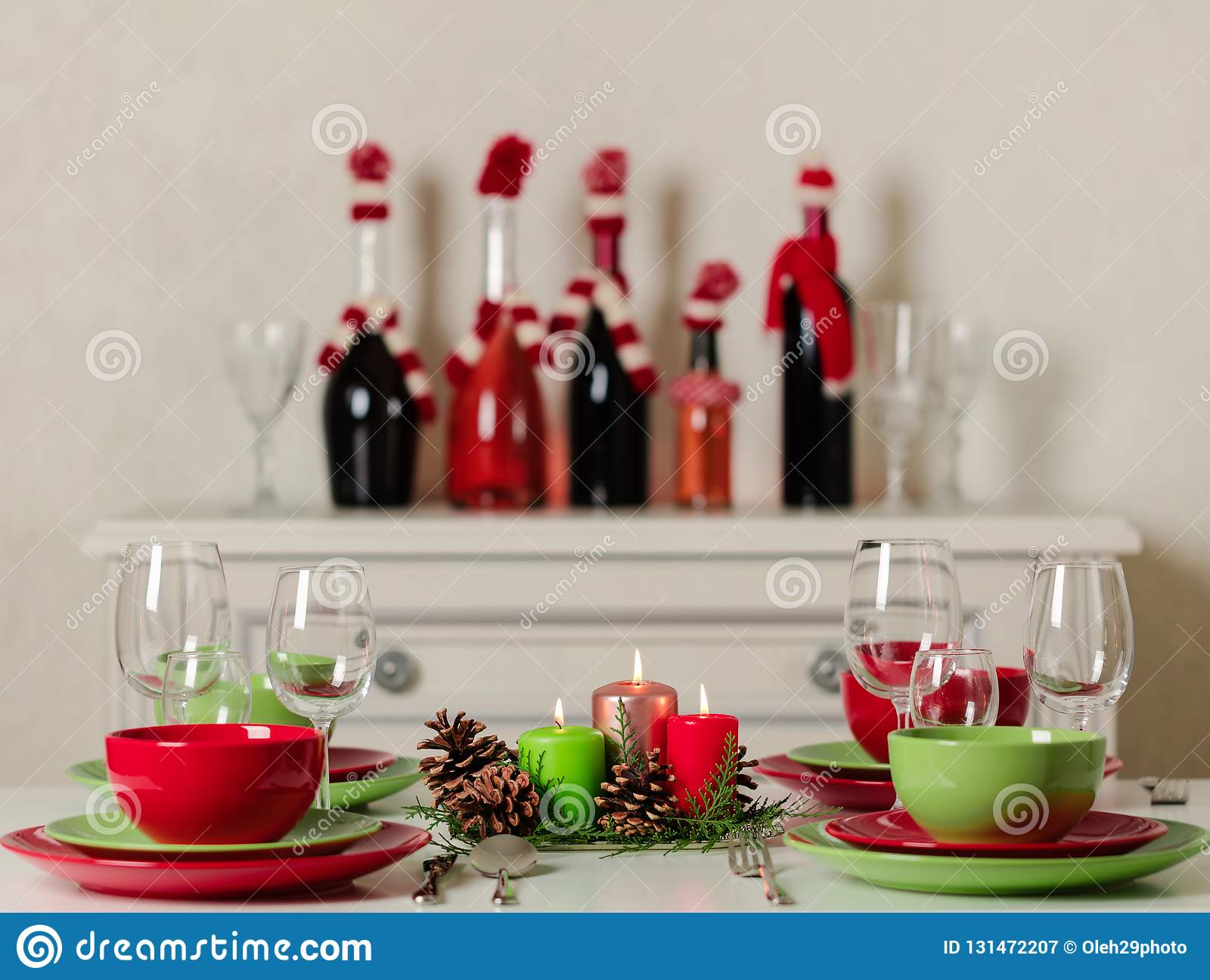 Merry Christmas and Happy New Year! Тable setting festive decor - green and red dishes, candles and fir cones. Knitted decor -