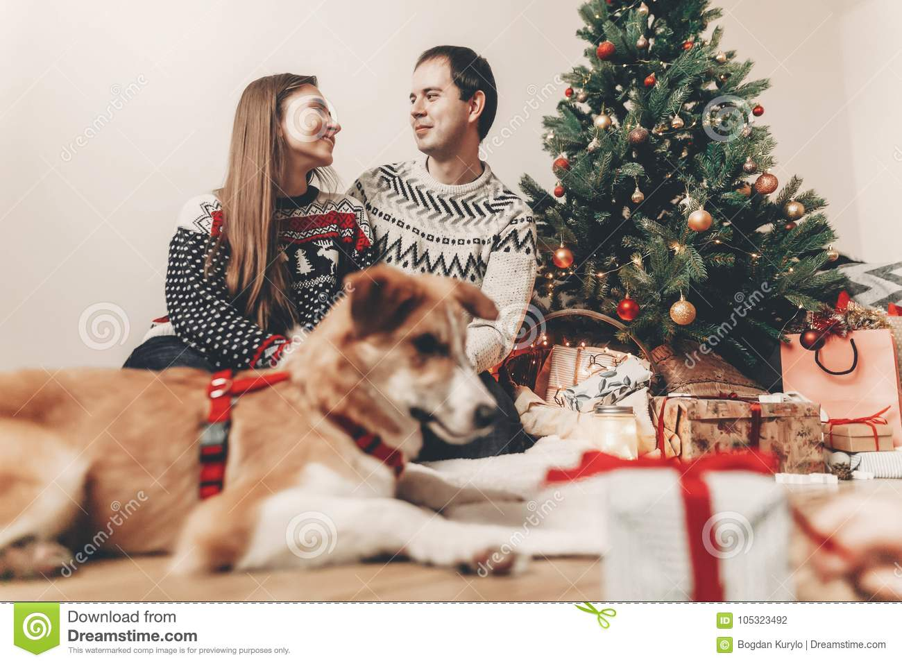 merry christmas and happy new year concept. happy family in stylish sweaters and cute dog at christmas tree with lights and gifts