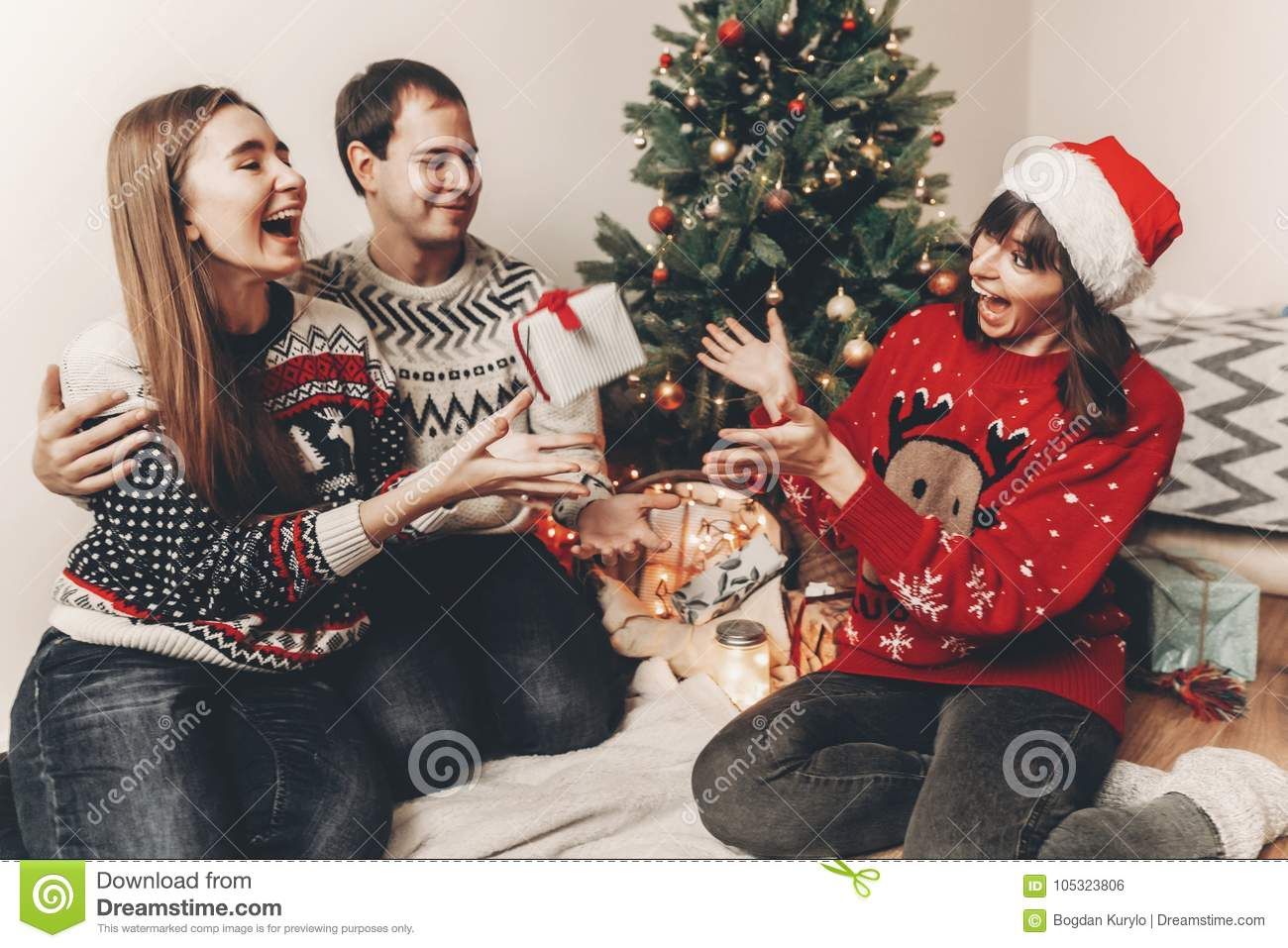 merry christmas and happy new year concept. stylish hipster family in festive sweaters exchanging gifts at christmas tree lights.