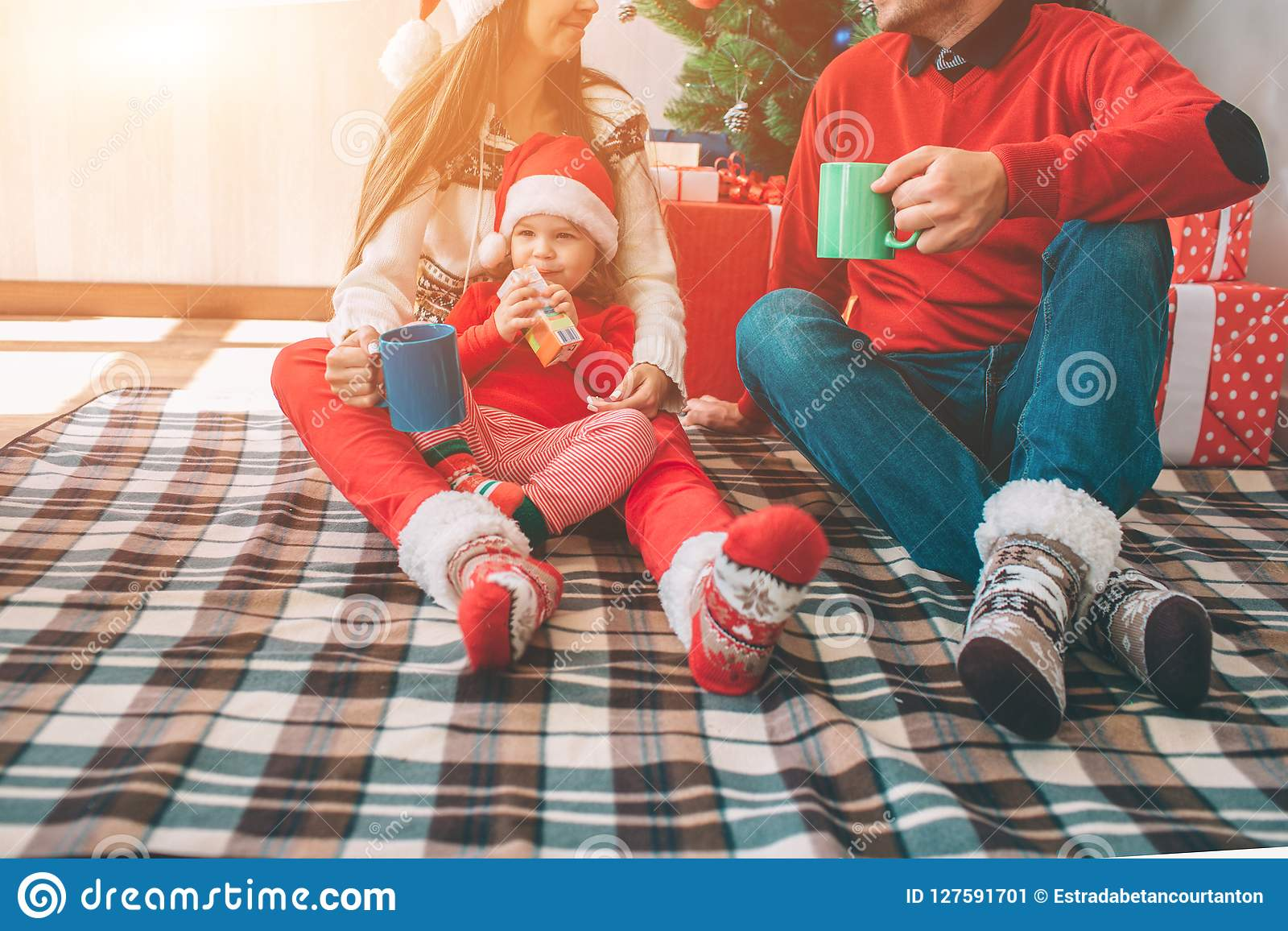 Merry Christmas and Happy New Year. Cut view of family sitting together on blanket. They wear colorful clothes. Man and