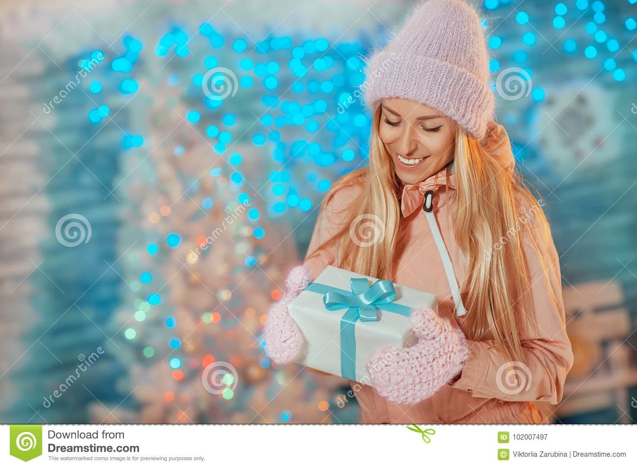 Merry Christmas and Happy New Year! Portrait of happy cheerful beautiful woman in knitted hat mittens holding holiday present box
