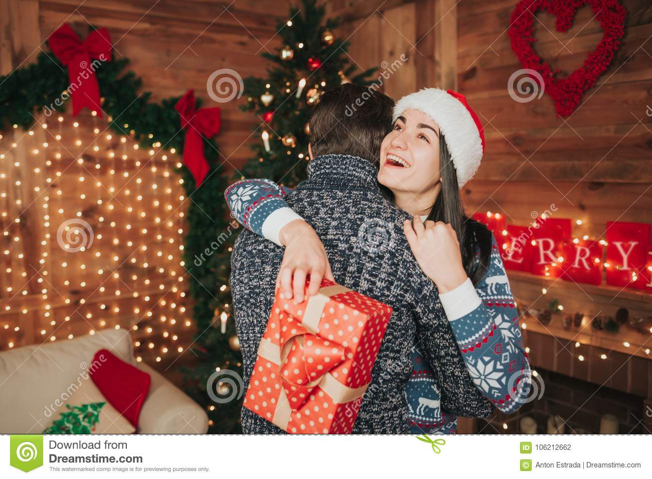 Merry Christmas And Happy New Year Young Couple Celebrating Holiday At Home Men Women Hug Give Each Other Gifts