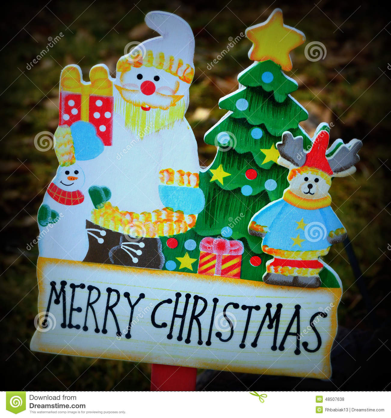 a hand painted wooden yard decoration with santa presents snowman teddy bear christmas tree with a star and words that say merry christmas