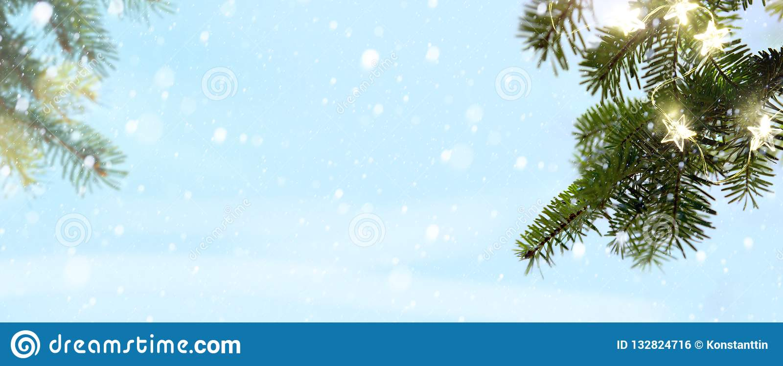 Merry Christmas - snow and fir tree branches with holidays light