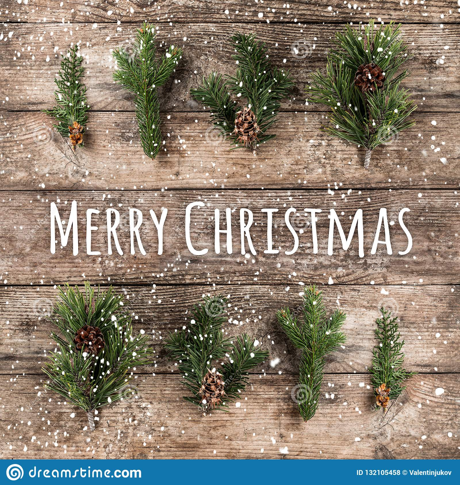 Merry Christmas Typographical on wooden background with fir branches, pine cones and snowflakes on wooden background. Xmas and New