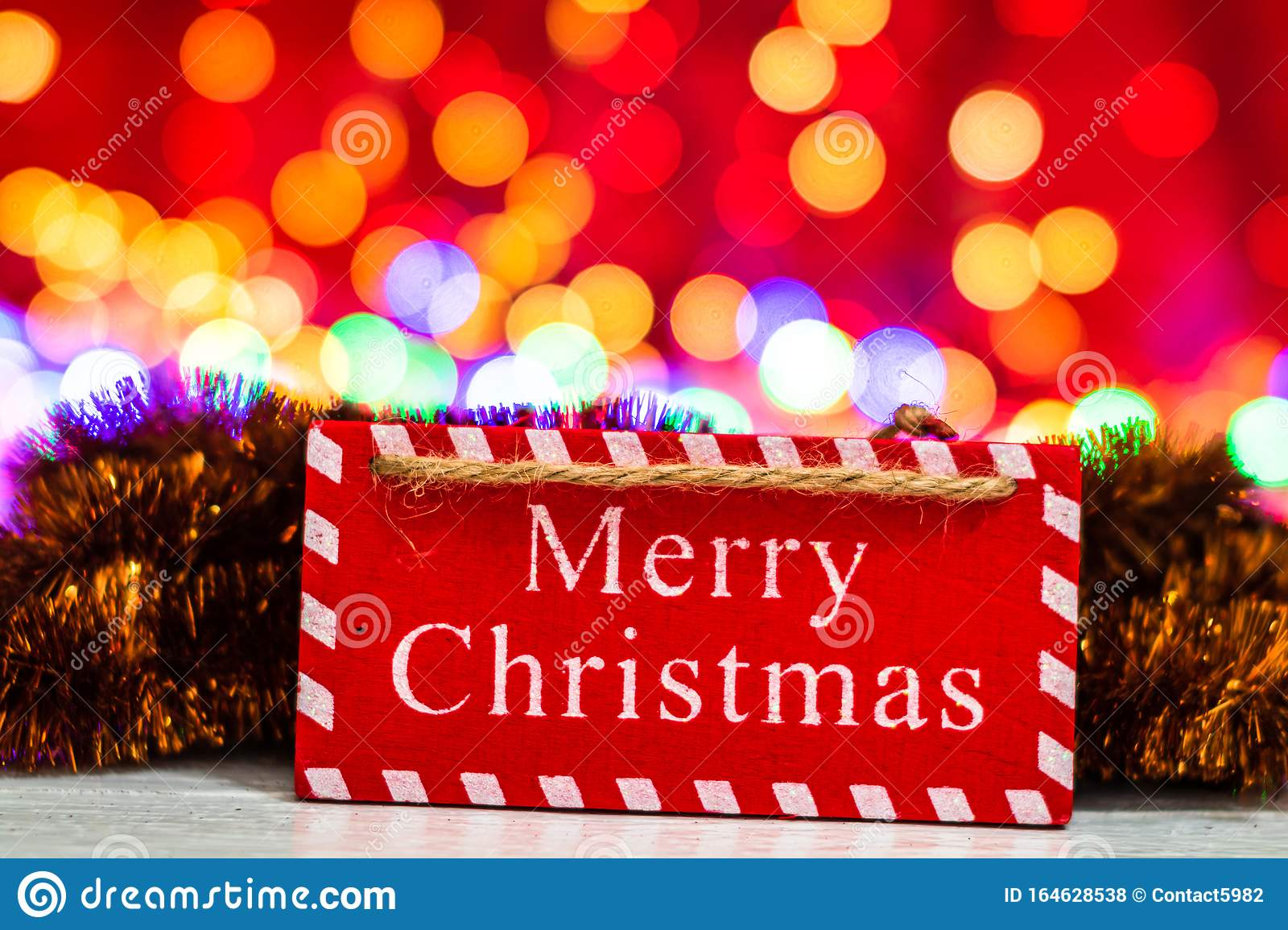 Merry Christmas wooden sign. Christmas composition on blurred lights background