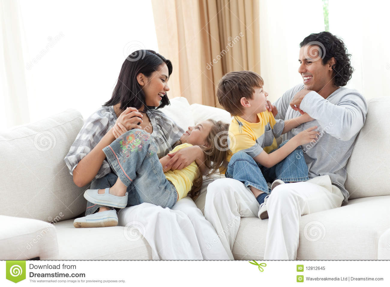 Merry family playing in the living room stock image for Family in a living room