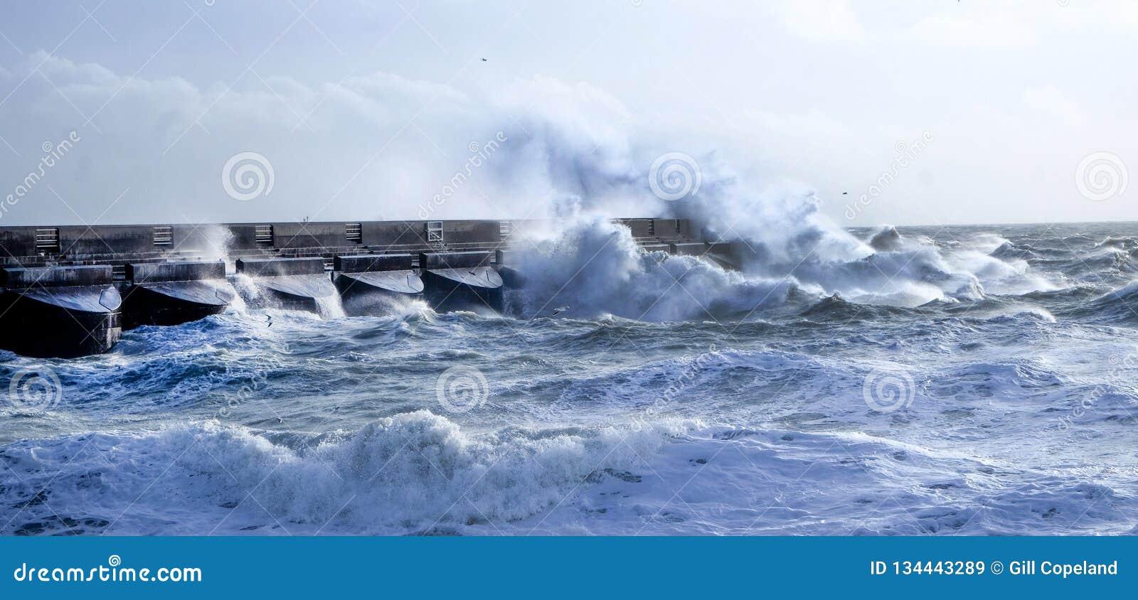 Mers agitées se brisant contre le mur de habour de marina de Brighton, R-U