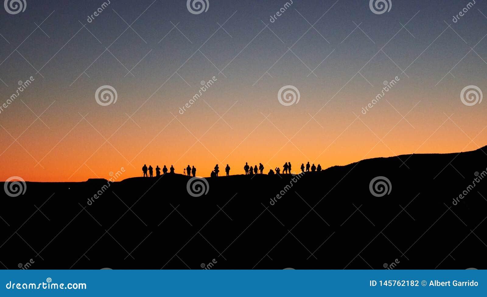Merzouga,摩洛哥- 2018年12月04日:由后照等待日出的很多人