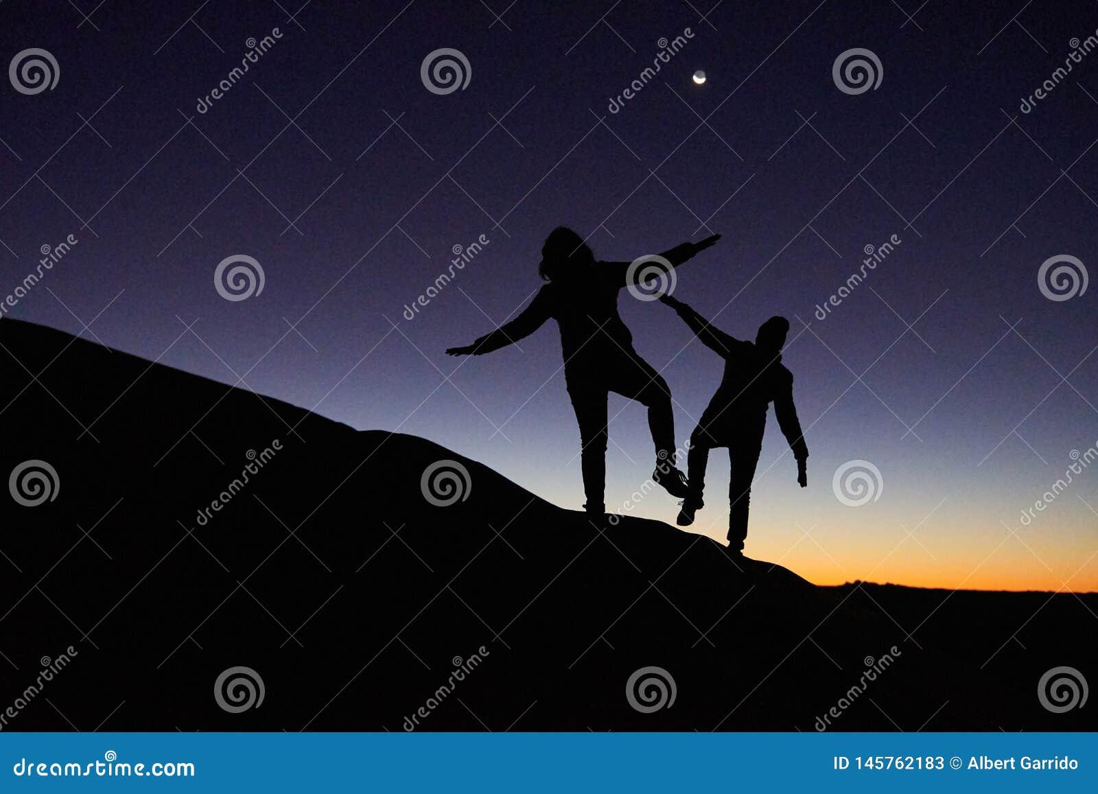Merzouga, Marokko - 4. Dezember 2018: Leute der Hintergrundbeleuchtung zwei, die eine Düne mit einem Sonnenaufgang klettern