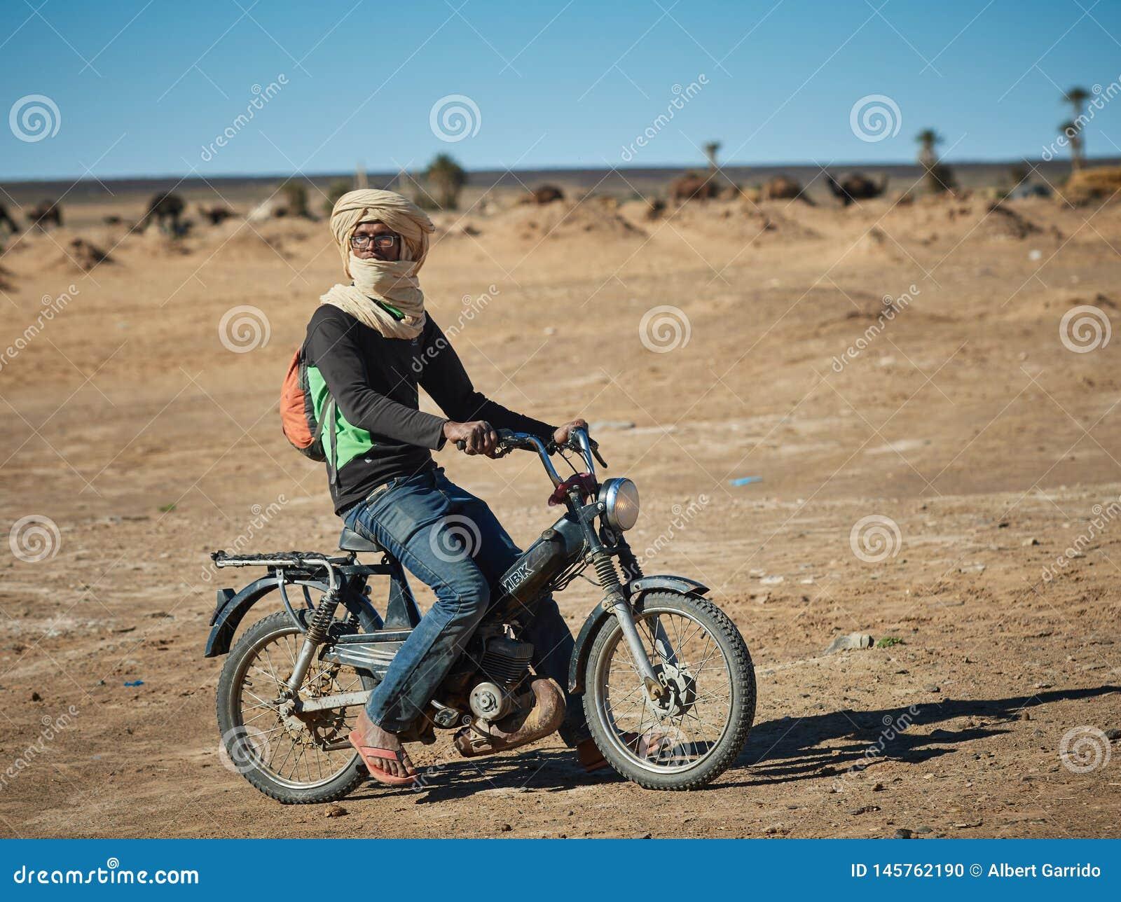 Merzouga Maroko, Grudzień, - 04, 2018: Berber na motocyklu po środku pustyni,