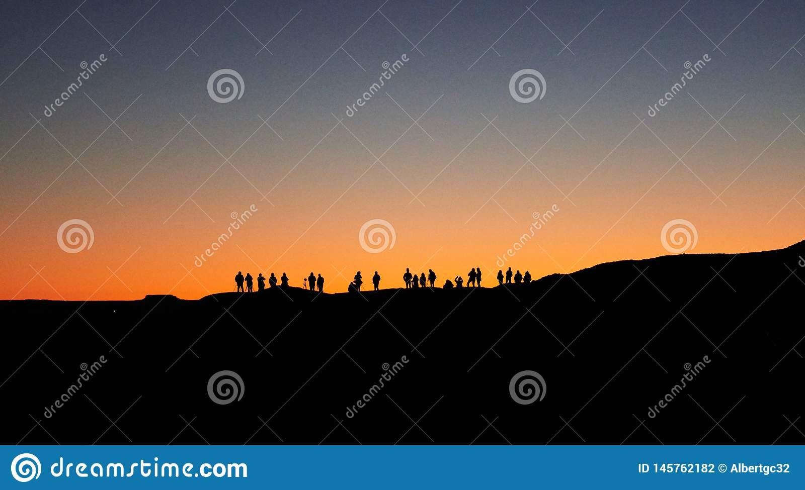 Merzouga, Morocco - December 04, 2018: backlight a lot of people waiting the sunrise