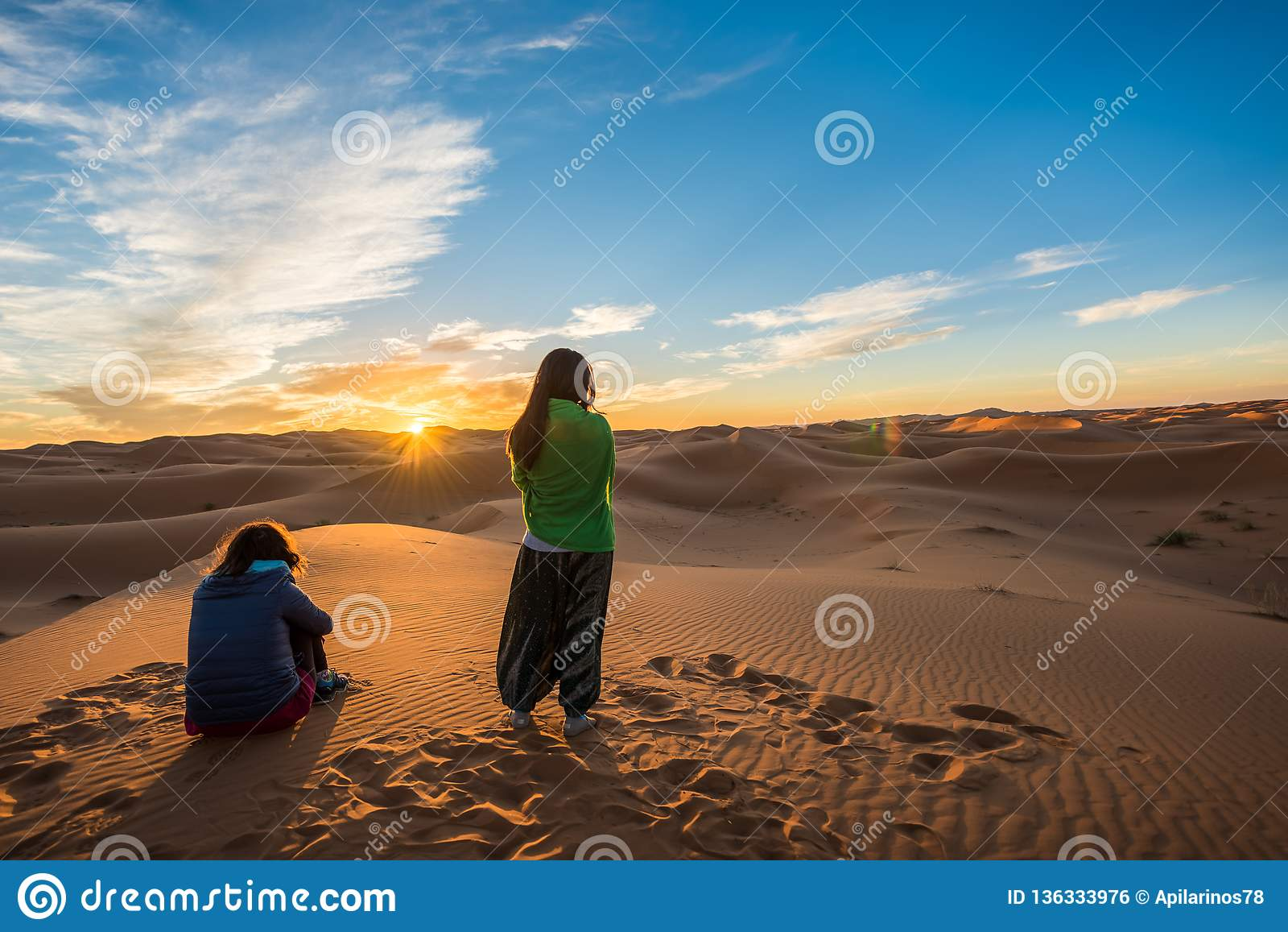 Merzouga, Morocco - October 16, 2018: Two women watching a beautiful sunrise over Erg Chebbi sand dunes near Merzouga, Morocco