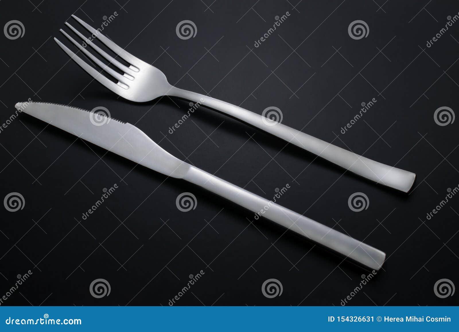 Mes en vork op zwarte achtergrond