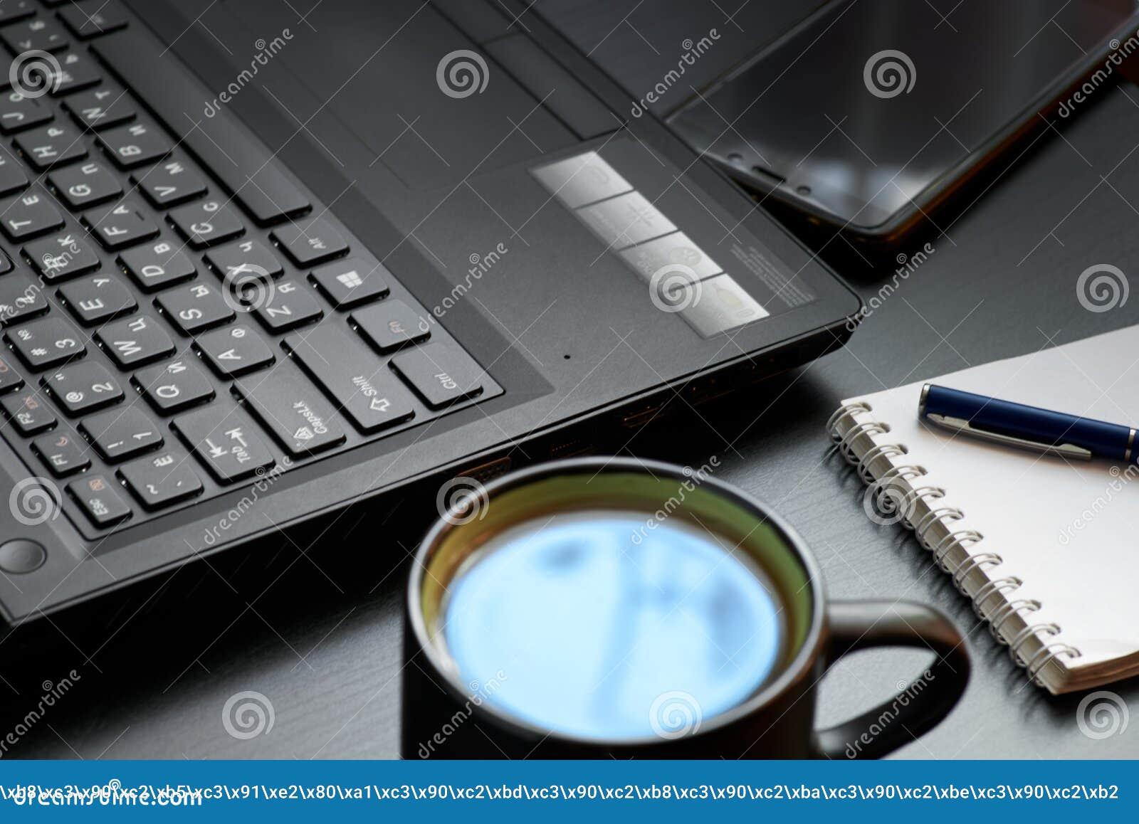 Mesa com portátil, o telefone esperto, os cadernos, as penas, os monóculos e um copo do chá Opinião de ângulo lateral