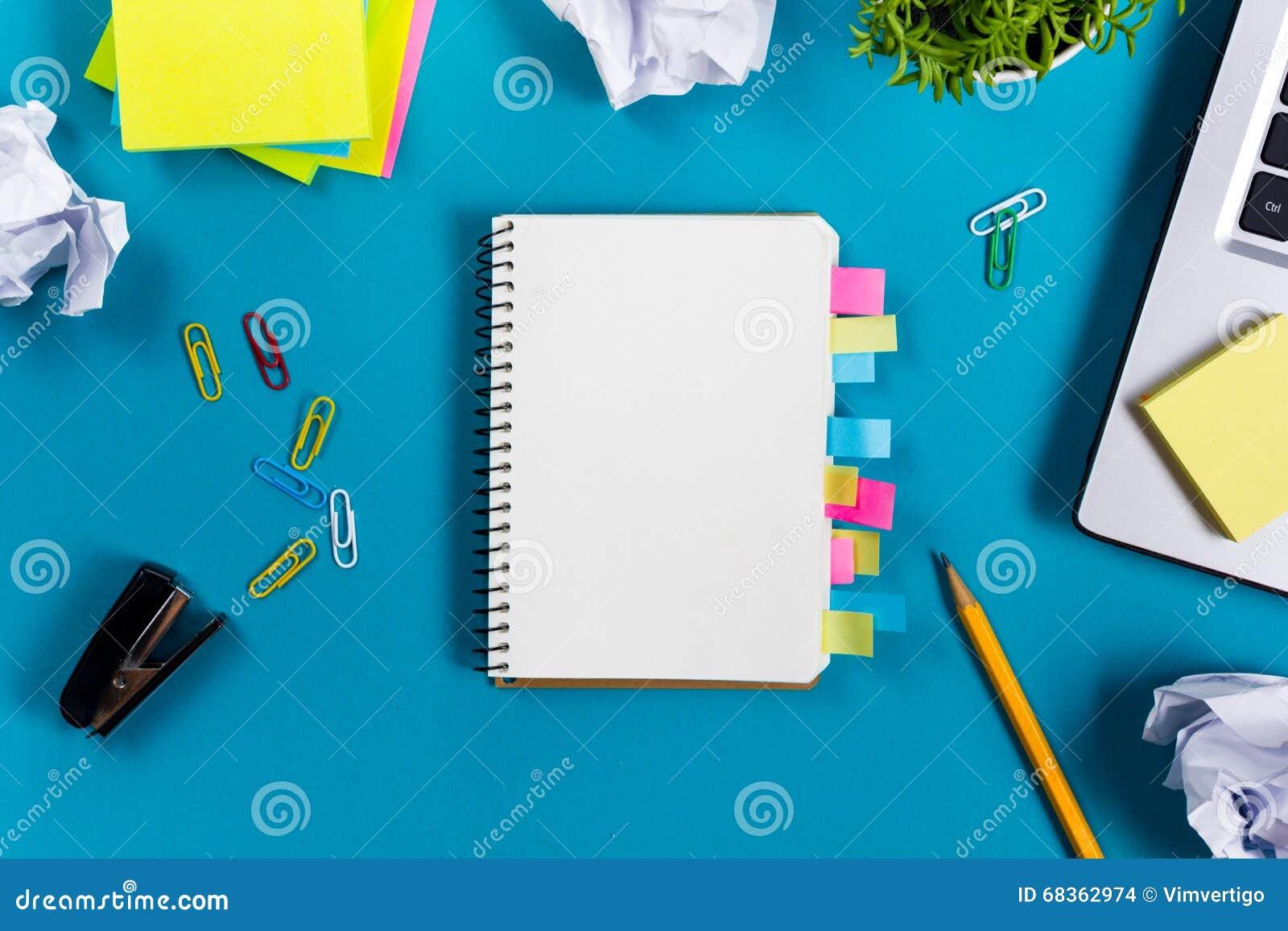 A mesa da tabela do escritório com grupo de fontes coloridas, almofada de nota vazia branca, copo, pena, PC, amarrotou o papel, f