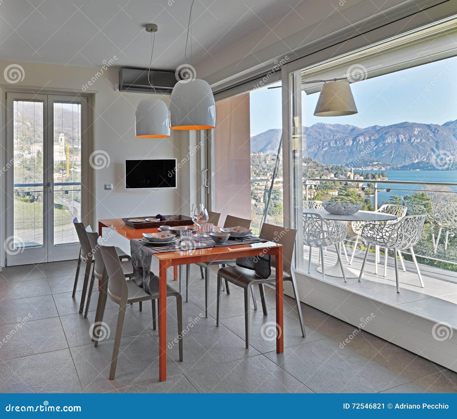 Mesa De Jantar De Vidro Alaranjada Na Cozinha Moderna Imagem De