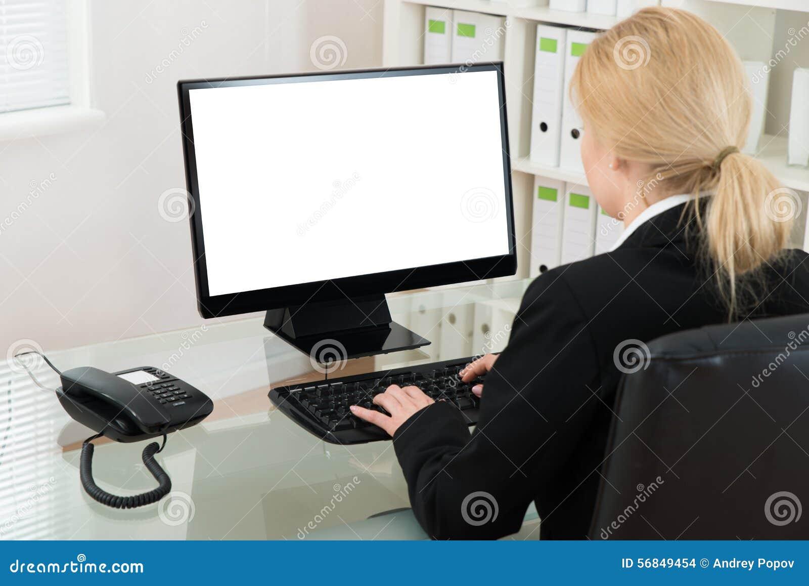 Mesa de Using Computer At da mulher de negócios