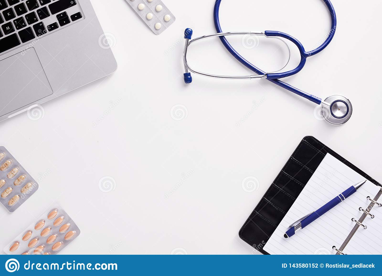Mesa médica com estetoscópio, latptop, comprimidos e papel vazio na prancheta
