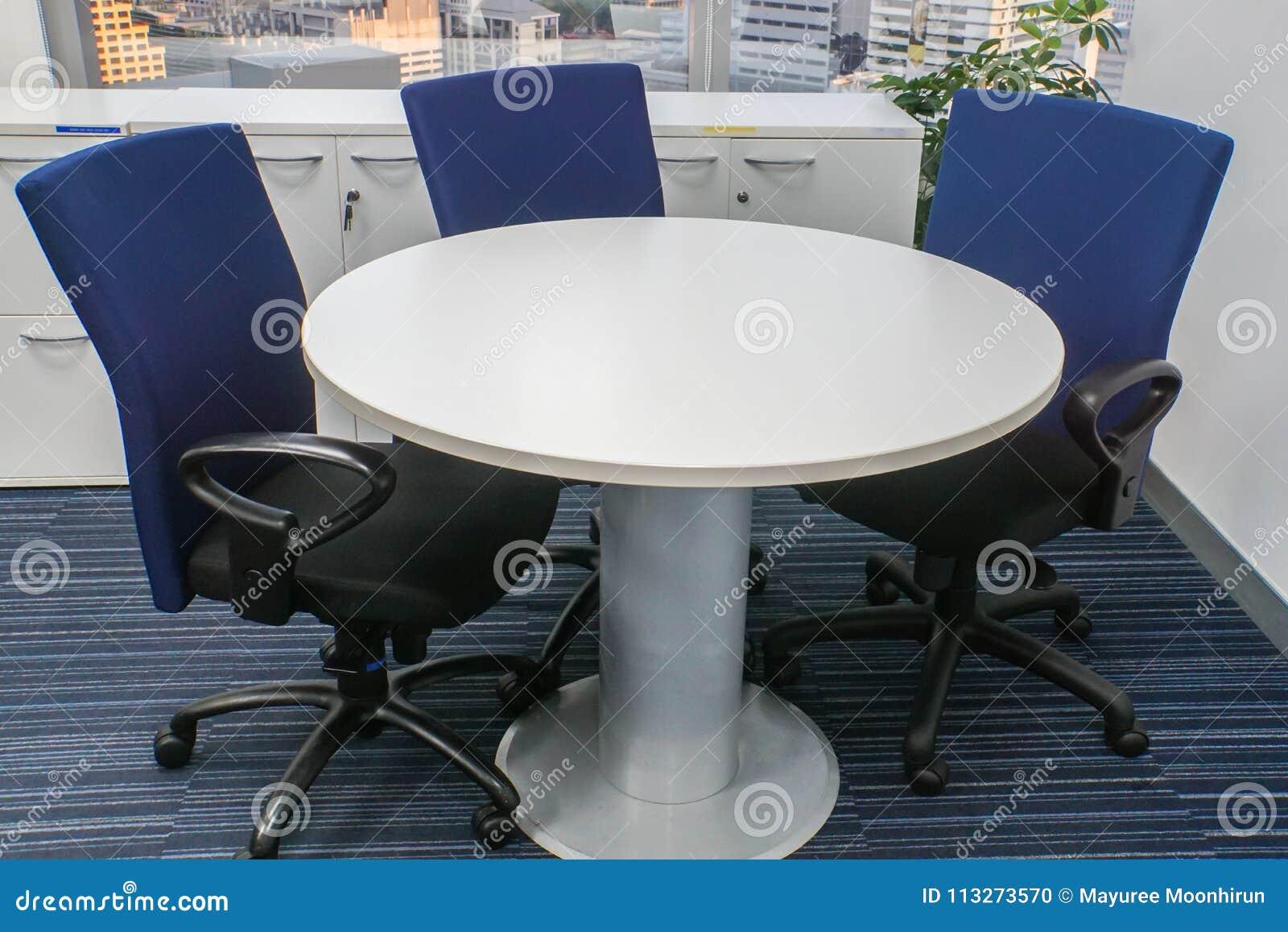 Mesa redonda blanca con las sillas azules para la reunión de la oficina