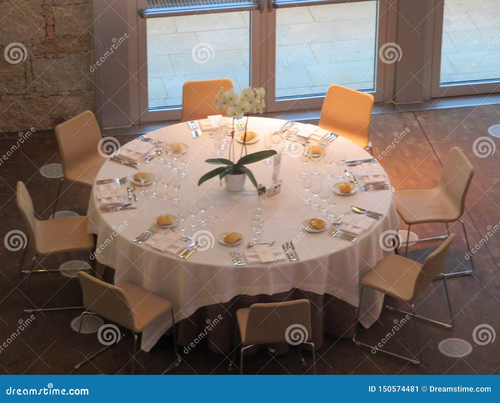 Mesa redonda bonita pronta para receber convidados e consegui-los comer