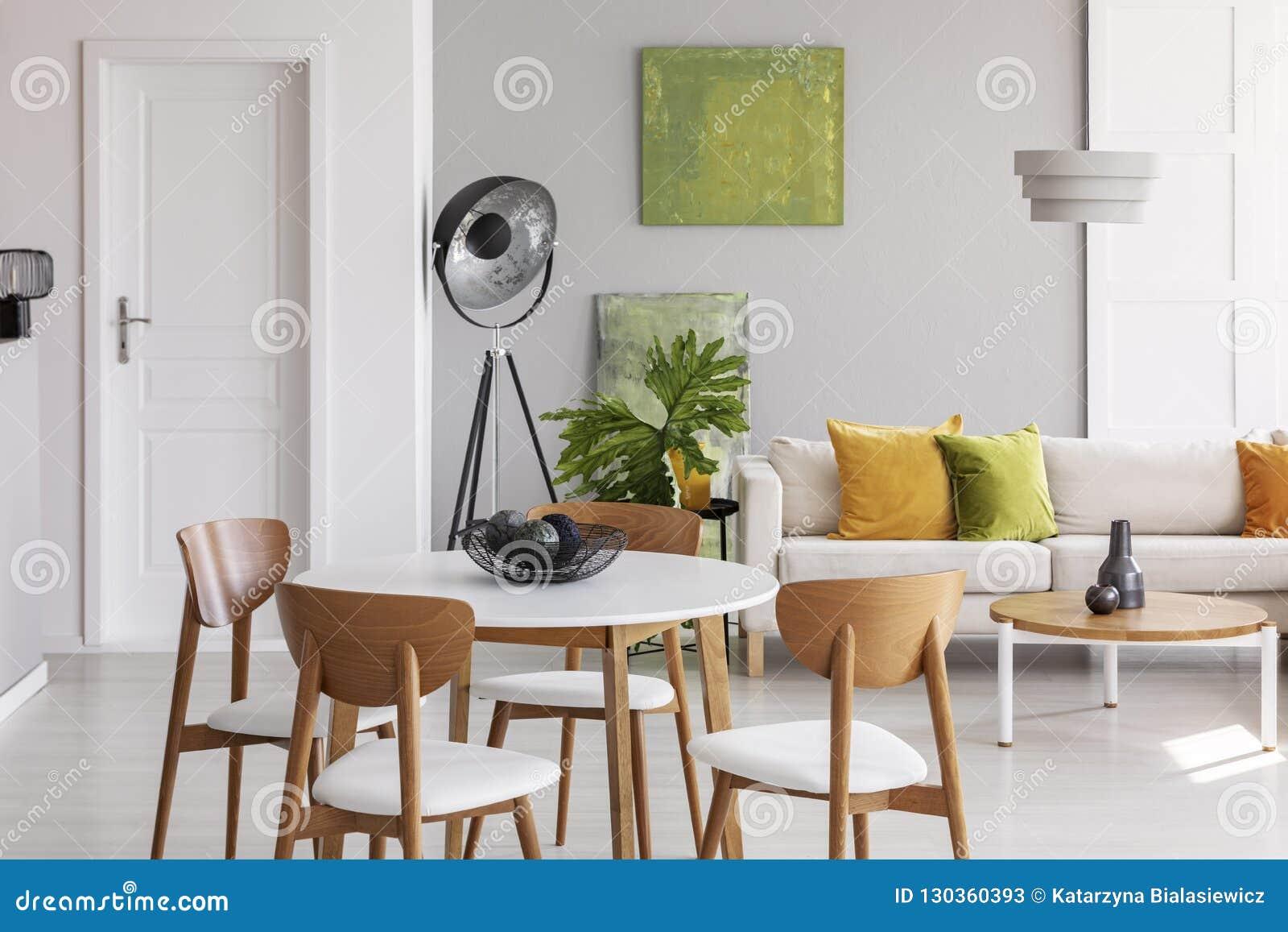 Mesa redonda branca com as cadeiras de madeira no meio da sala de visitas à moda com lâmpada industrial, o sofá confortável e cal