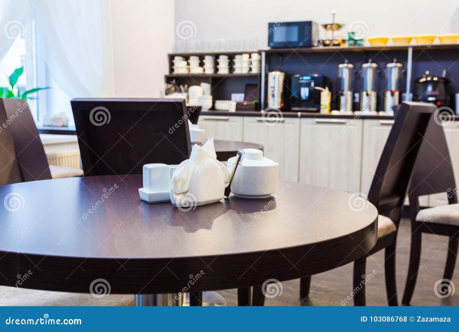 Mesa redonda e açucareiro de madeira, guardanapo, sal e pimenta no café moderno com mobília da cozinha no fundo interior