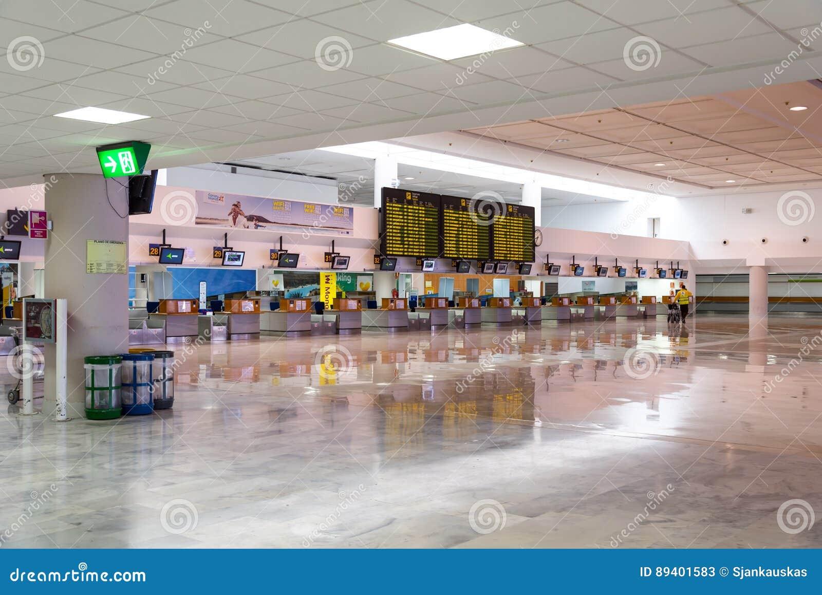 Mesas de registro do salão da partida no aeroporto de Arrecife