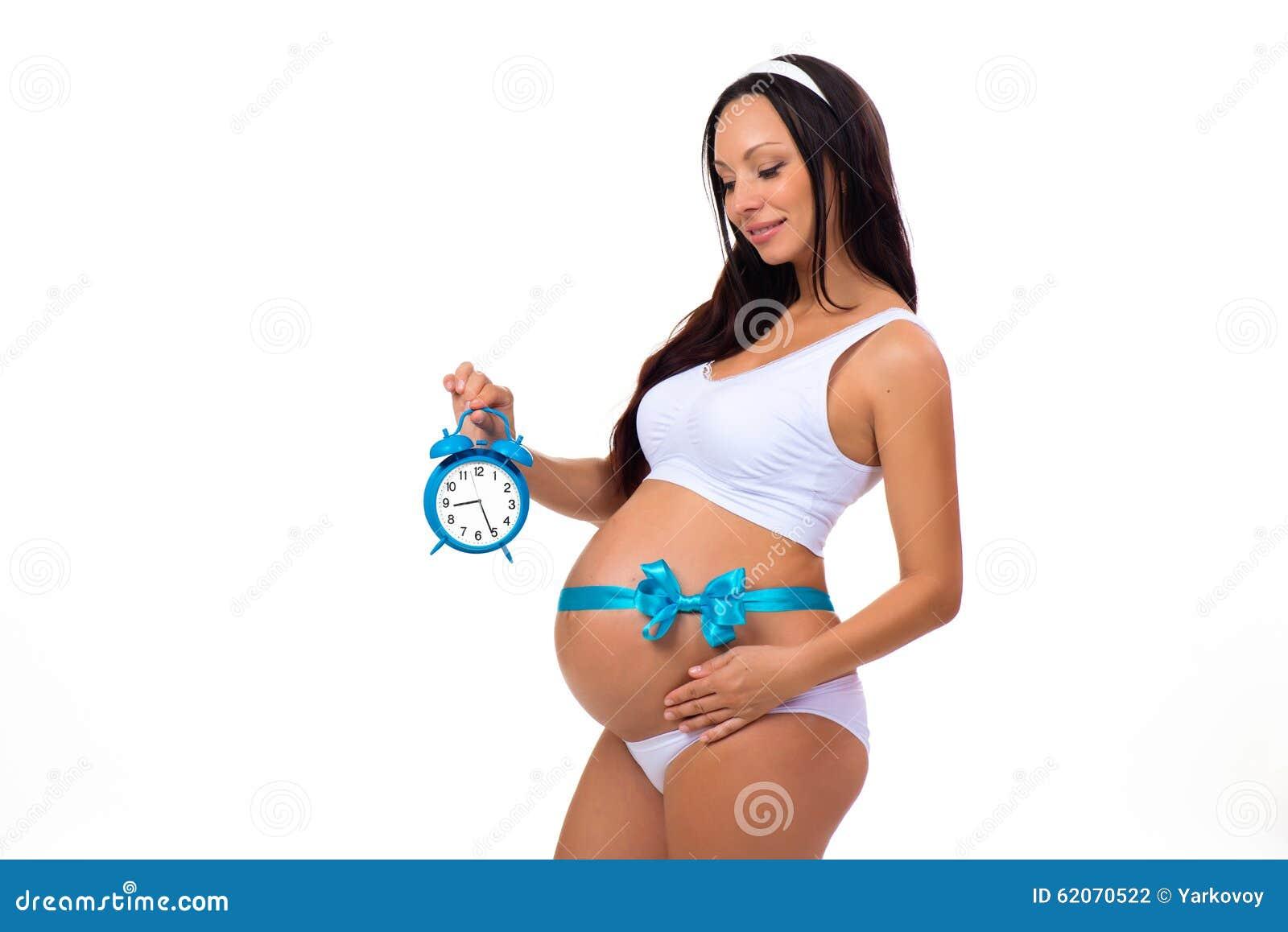 9 meses Gravidez feliz Mulher gravida com o despertador em suas mãos e  curva azul na 731b25a32d