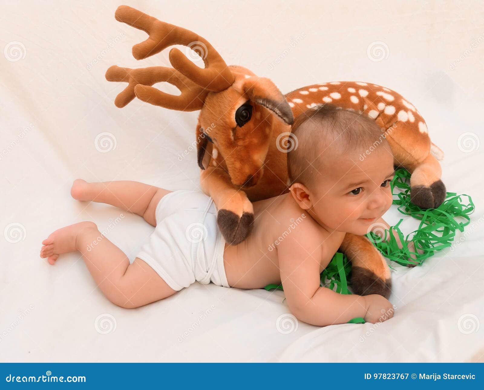 866a11747b 4 mesi del neonato che gioca con il giocattolo molle caro ed il fondo di  bianco del pulcino. Più immagini stock simili