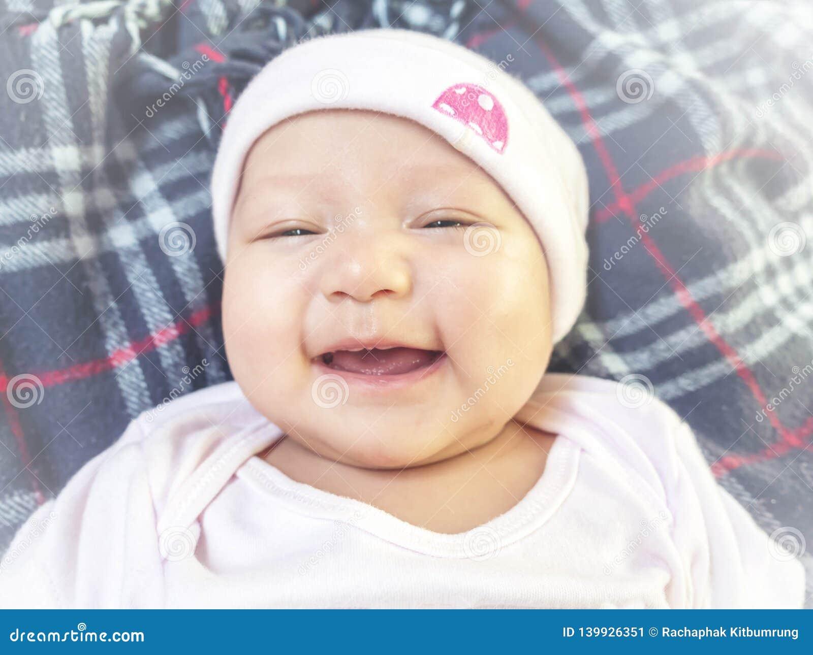 4 mesi di neonata che ride alla macchina fotografica Piccolo gilr allegro in tuta rosa e cappello che mette sul letto che ride a