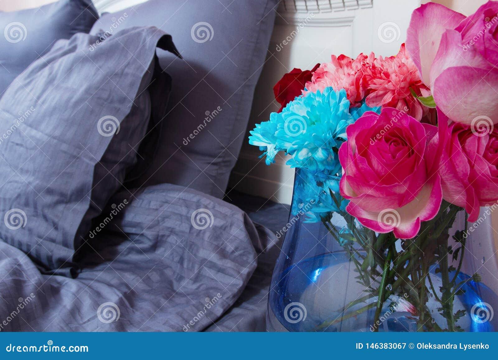 Mesita de noche con el florero de rosas de las flores y de aire fresco del dormitorio Cama con linos azules, manta, almohadas por