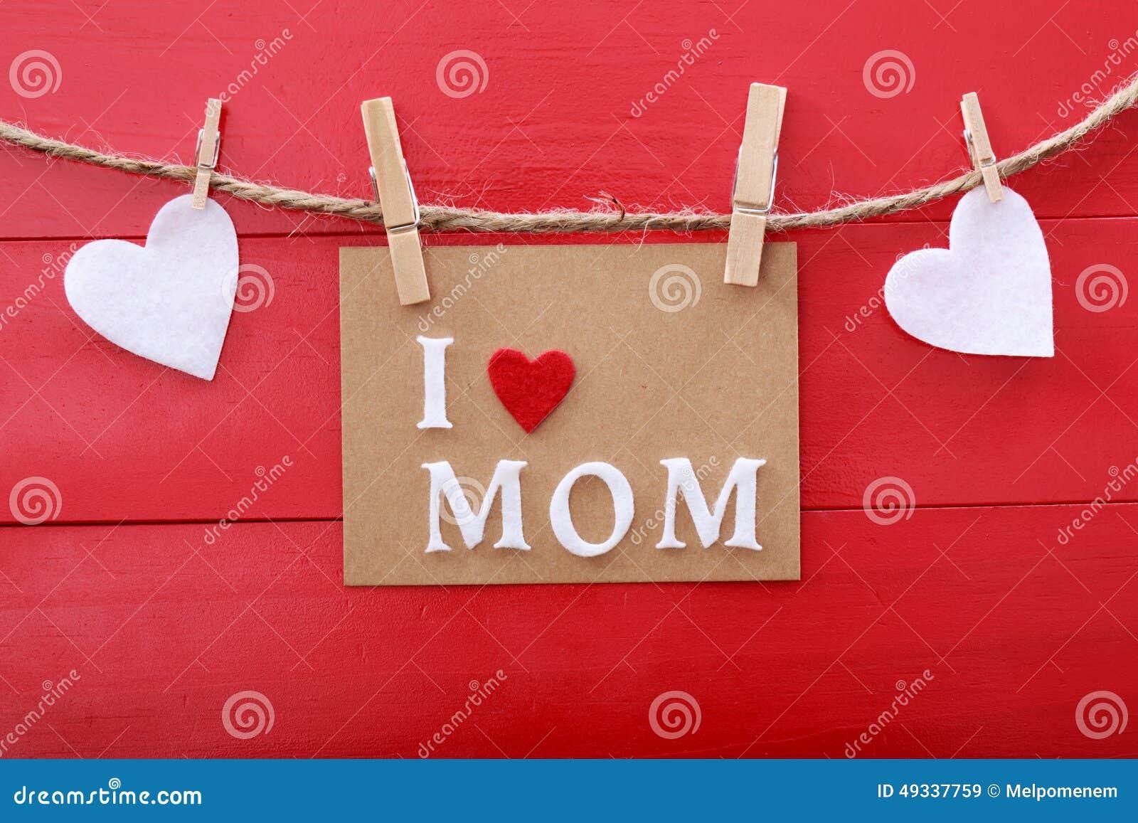 Message de jour de mères avec des pinces à linge au-dessus de conseil en bois rouge