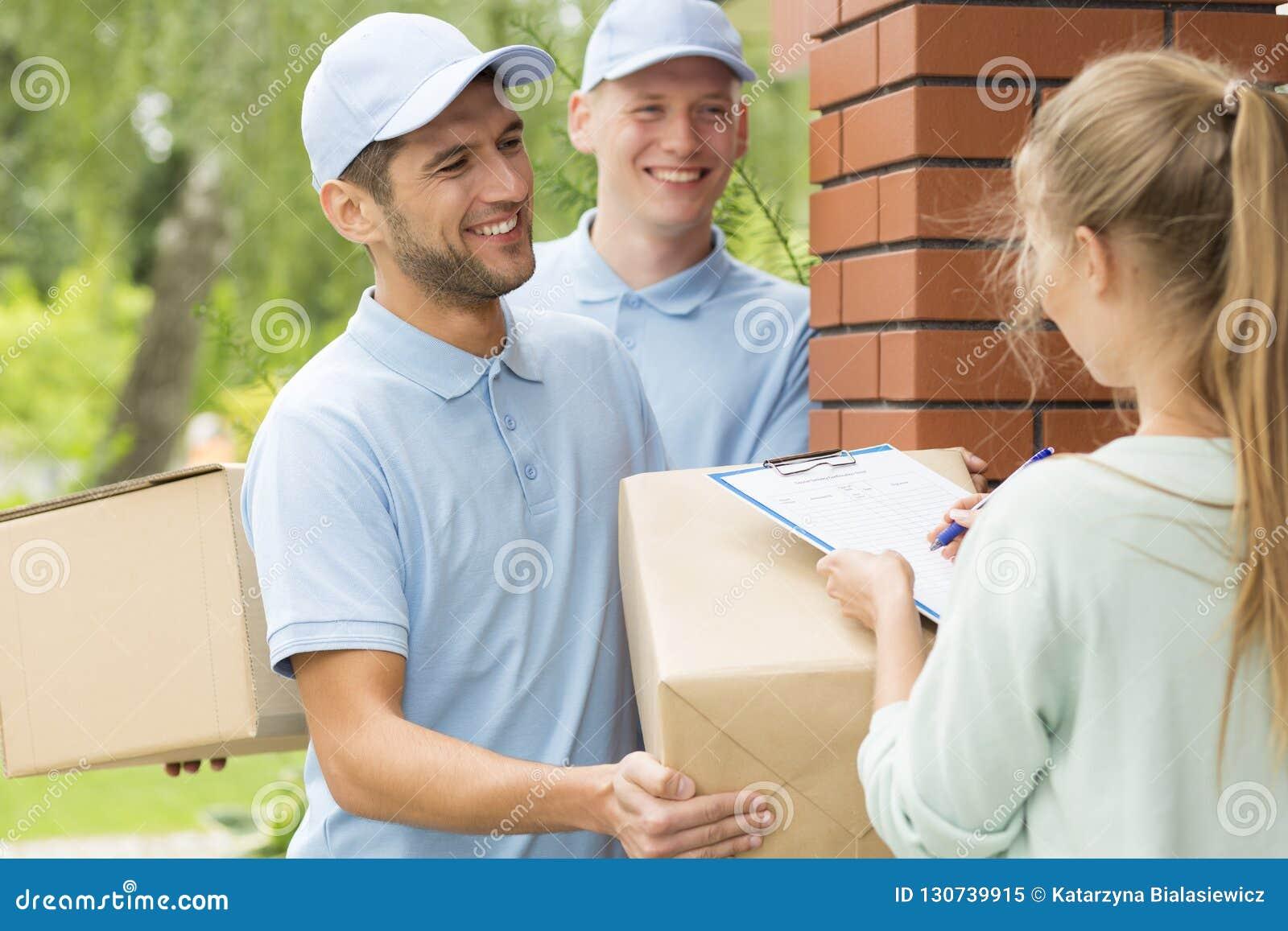Messagers de sourire dans les uniformes bleus et les jeunes femmes remplissant vers le haut des documents de la livraison