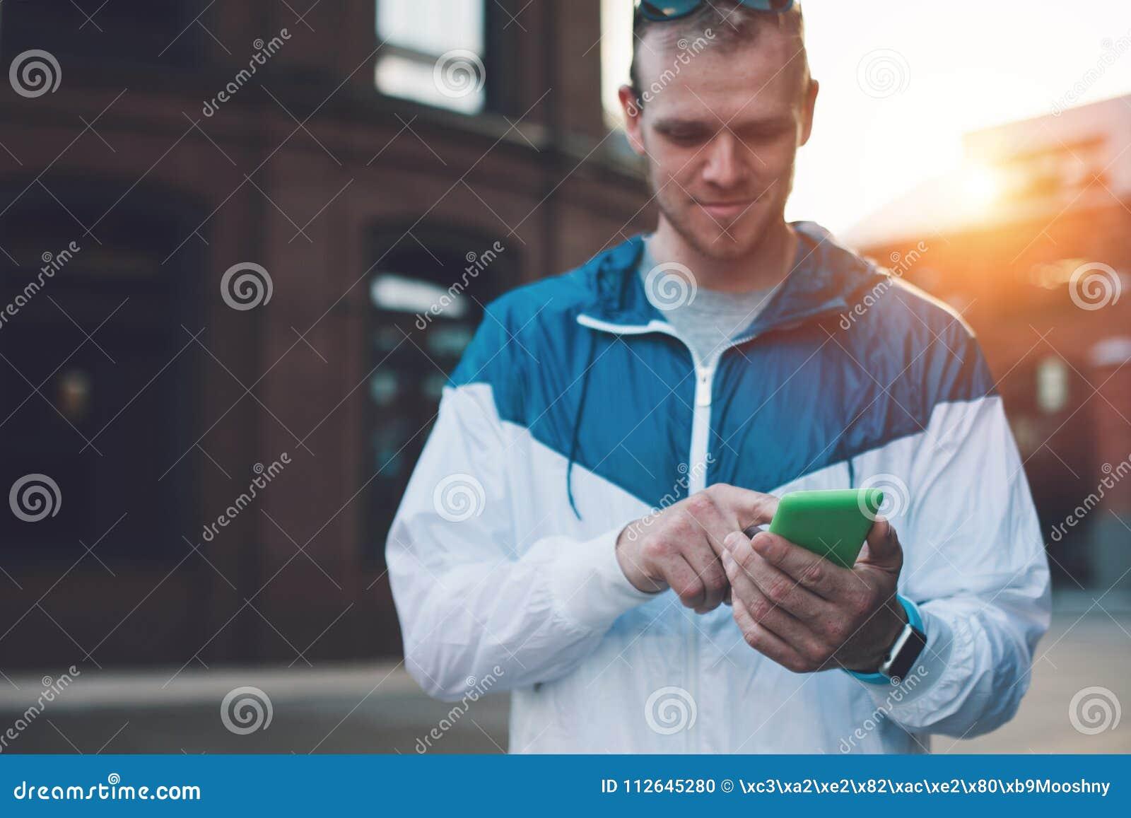 Messaggio di battitura a macchina bello sul suo telefono cellulare, tramonto del giovane sulla via
